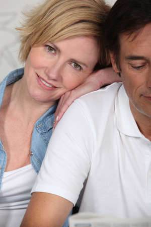 foreplay: Couple lying dressed on their bed Stock Photo