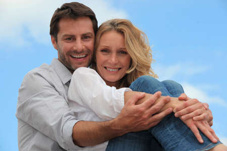 active couple: Couple sat hugging each other in park Stock Photo