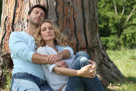 2 50: Couple sleeping under a tree Stock Photo