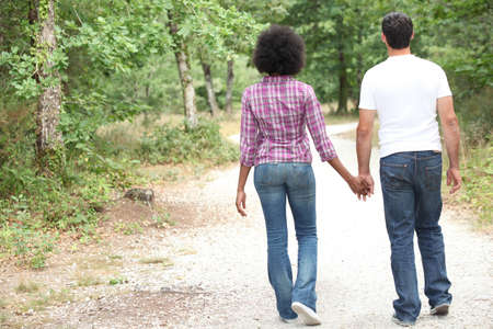 mixed race couple: Couple walking in a forest Stock Photo