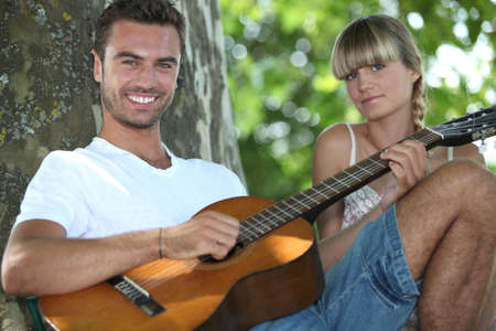 Man with acoustic guitar playing to girlfriend in park Stock Photo