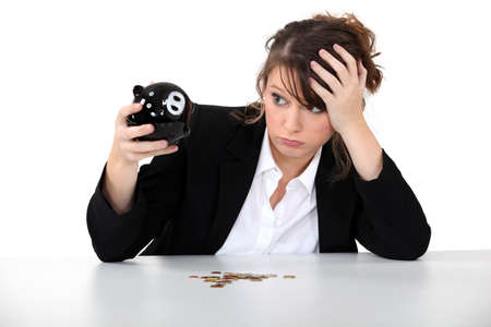 few: Young desperate woman with her piggy bank Stock Photo