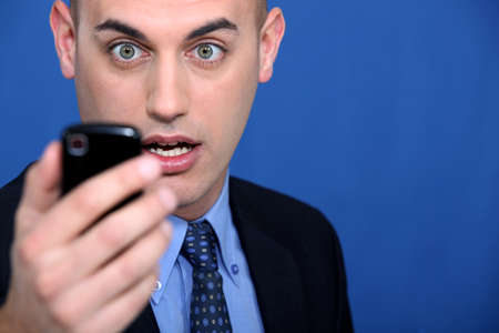 Shocked man looking at mobile telephone photo
