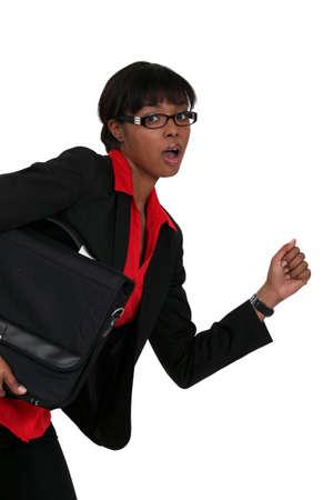An African American businesswoman running. photo