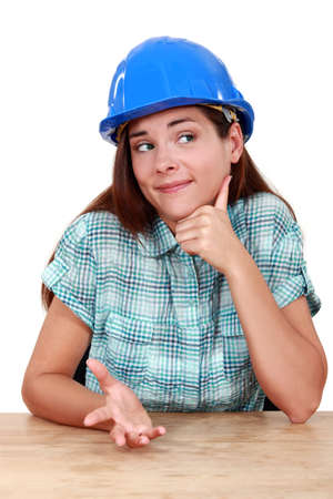 blase: Thoughtful woman in a hardhat sitting at a desk