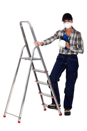 Tradesperson holding a spray gun and standing next to a stepladder photo