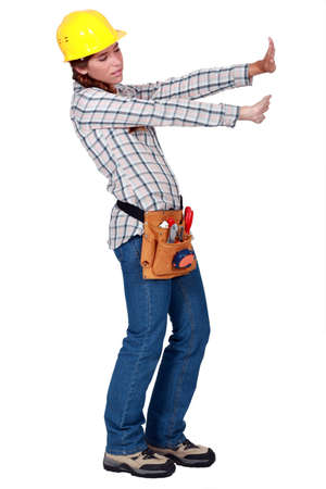 drowsiness: Tradeswoman pushing up against an invisible wall Stock Photo
