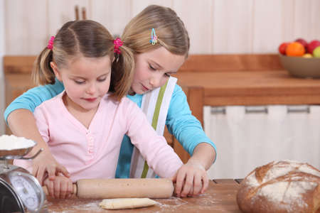 Sisters using rolling pin to roll dough photo
