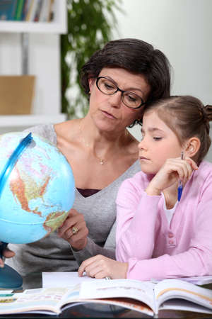 half globe: mother holding a globe and giving explanations to her daughter Stock Photo