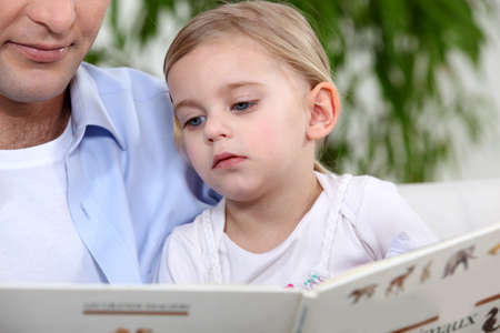 Father and daughter reading book photo
