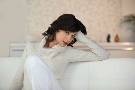 chic woman: Chic woman sitting on a white sofa Stock Photo