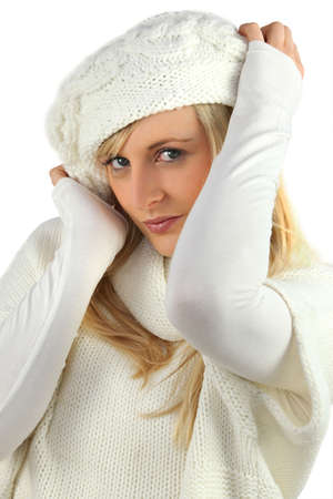 pretty coquettish young blonde wearing white cardigan and bonnet Stock Photo