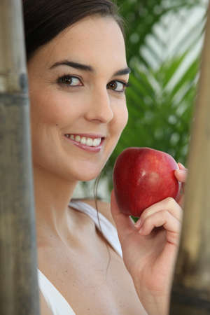 Woman eating a red apple amongst bamboo photo
