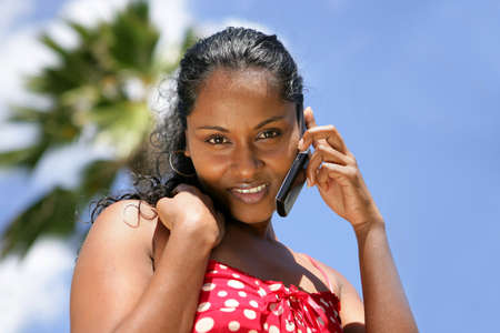 black lady talking: beautiful African woman on vacation talking on her cell Stock Photo
