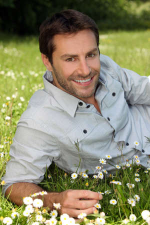 35 39 years: Closeup of smiling man amongst the daisies