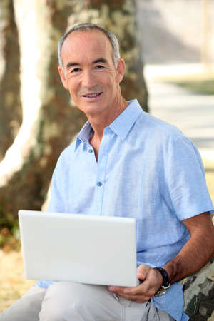 grey haired: Grey haired man in park with laptop computer