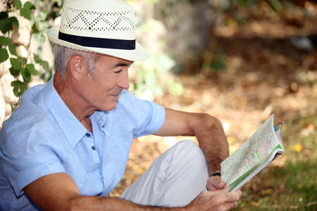 65 years old: 65 years old man sitting in the grass and watching a book