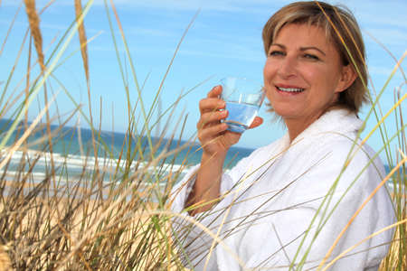 45 50 years: Woman drinking a glass of water by the seaside