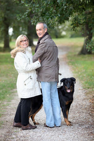 couple of pensioners walking their dog Stock Photo - 11946782