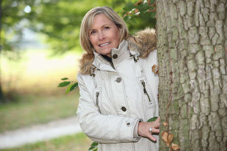 55 59 years: Woman out for an autumn stroll in the woods