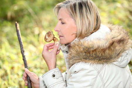 sniffing: Woman sniffing mushroom Stock Photo