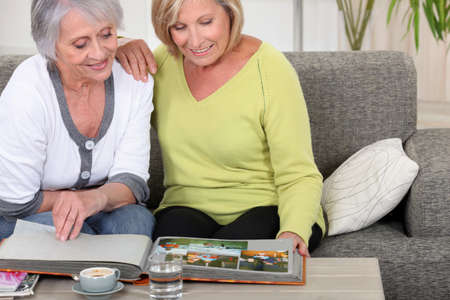 mature women skimming through family album photo