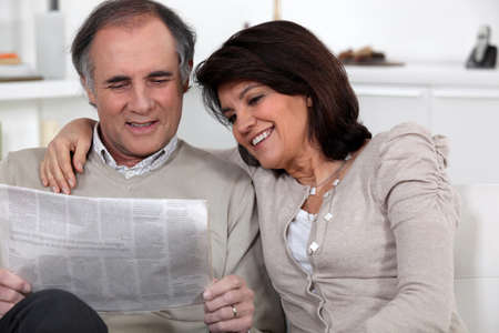 Couple reading newspaper photo