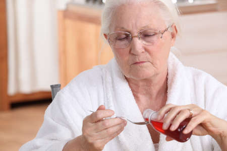 taking medicine: Senior woman taking cough syrup