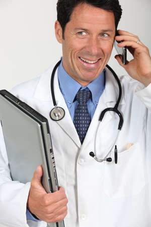 A doctor holding a laptop and having a conversation via his mobile phone. photo
