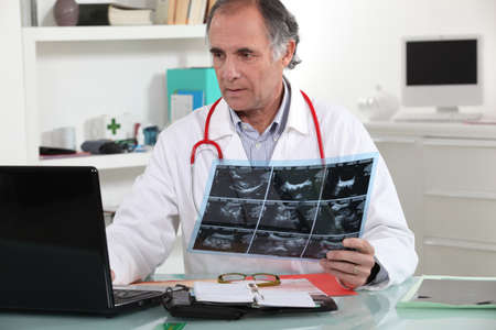 55 60 years: Doctor entering x-ray results into his database Stock Photo