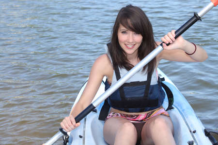 safety jacket: #young brunette in kayak Stock Photo