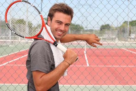 bel homme: L'homme se tenait devant la cour de tennis tenant raquette sur l'�paule