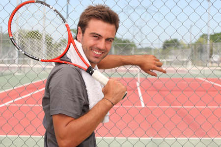Man stood in front of tennis court holding racket over shoulder photo