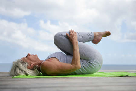 Woman doing yoga on jetty Stock Photo - 11948030