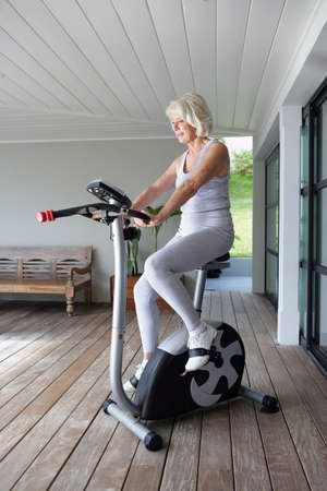 Elderly woman on an exercise machine photo
