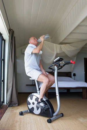 Man cycling on machine at home photo