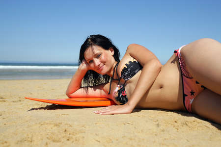 watersports: Brunette laying seductively on surfboard Stock Photo