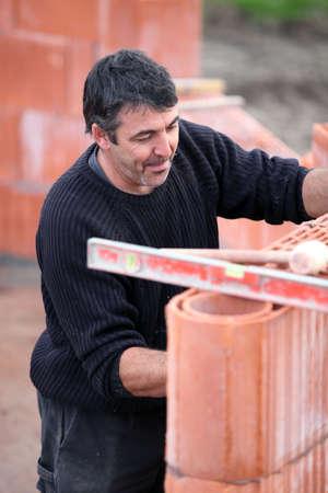 Stonemason constructing a wall photo