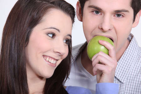 garden of eden: young man eating apple and girlfriend Stock Photo