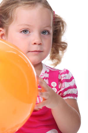 poker faced: Little girl holding a balloon Stock Photo