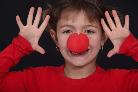 little girl with red nose playing clown photo
