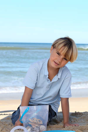 eight years old: Little boy collecting starfish in a bucket on the beach