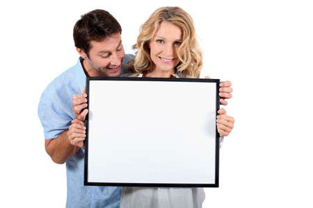 Couple holding white board photo