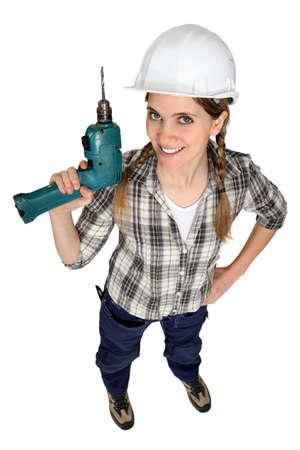 taladro: Un trabajador de la construcción femenina sosteniendo un taladro.