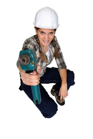 Tradeswoman holding up a power tool photo