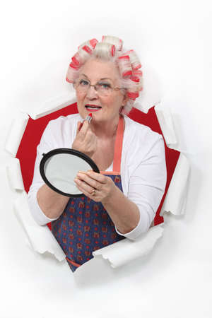 transitional: Old woman in rollers putting on lipstick Stock Photo