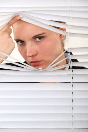 Woman looking through venetian blinds photo