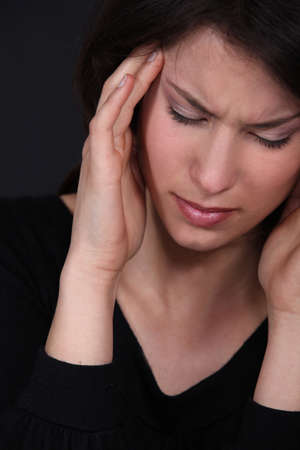 cephalgia: Woman suffering from a throbbing headache