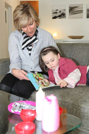 Woman and little girl reading a book photo
