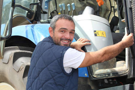 portrait of a farmer climbing on tractor photo